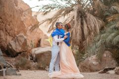Bride and groom wrapped in flag of Ukraine are kissing in canyon. Bride and groom wrapped in flag of Ukraine are kissing in canyon against backdrop of palm Stock Photo