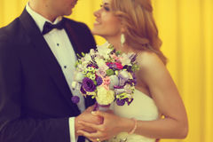 Bride and groom on a yellow background. Holding flower bouquet Stock Photo