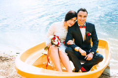 Bride and groom in yellow boat on water Stock Image