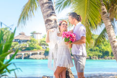Bride and groom, young loving couple, on their wedding day, outd. Oor beach wedding on tropical beach and sea background Stock Image
