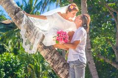 Bride and groom, young loving couple, on their wedding day, outd. Oor beach wedding on tropical beach and sea background Stock Photo