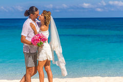 Bride and groom, young loving couple, on their wedding day, outd. Oor beach wedding on tropical beach and sea background Stock Images