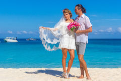Bride and groom, young loving couple, on their wedding day, outd. Oor beach wedding on tropical beach and sea background Royalty Free Stock Photos