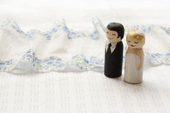 Bride and groome cake topper wooden doodle figures on white fabr. Ic background with laces Royalty Free Stock Image
