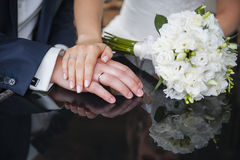 Bride and grooms hands with wedding rings Stock Photography
