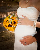 Bride and grooms hands wrapped around the brides baby bump and holding sunflower bouquet. royalty free stock photography