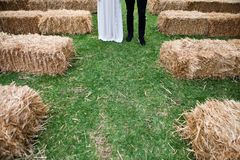 A bride and grooms legs stand in the wedding aisle that is made. Of haystacks on green grass field stock photo