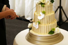 Bride and grooms wedding cake. The wedding cake at a formal marriage celebration is cut as is the tradition Royalty Free Stock Image