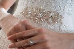 Bride in guipure dress and a brooch at the waist, close-up Stock Image