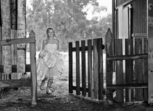 Bride in Gumboots. Young bride wearing gumboots under her wedding dress running through a farm gate Royalty Free Stock Photography