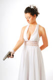 Bride with gun isolated on white. Pretty bride is aiming a silver pistol downwards in the standing position. White low-necked dress accentuates her beautiful Royalty Free Stock Photos