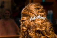 Bride at Hair Salon. Back of the bride's hair.  She has a pretty rhinestone comb in her hair.  The blurred reflection in the mirror is darkened to put the Stock Photography