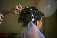 Bride hairstyle with white silk roses. Getting young bride ready and making hairstyle Stock Image