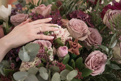 Bride hand with a gold ring holding a wedding flowers bouquet. Stock Photos