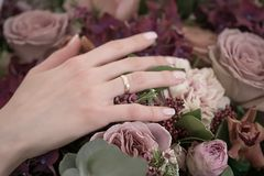 Bride hand with a gold ring holding a wedding flowers bouquet. Stock Image