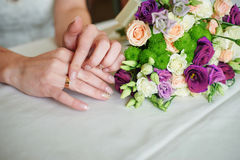 Bride hand with gold ring a wedding bouquet on table Royalty Free Stock Photography