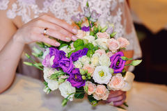 Bride hand with gold ring a wedding bouquet on table Royalty Free Stock Photos