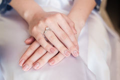Bride hand with manicure on wedding dress Royalty Free Stock Images