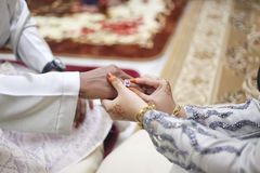 Bride hand putting a wedding ring on the groom finger Stock Photos