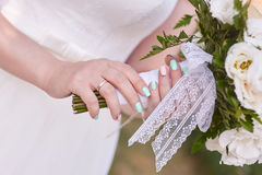 Bride hand with ring holding a bridal bouquet of white roses Stock Photography