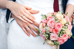 Bride hand with ring and wedding bouquet of flowers Royalty Free Stock Image