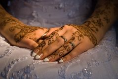 Bride hands. With rings and tattoo on a wedding dress Royalty Free Stock Photos