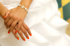 Bride hands. Abstract image of bride hands with orange fingernails over white wedding dress Stock Images
