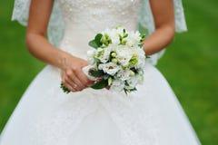 Bride hands holding bouquet Stock Images