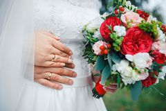 Bride hands with ring and wedding bouquet of red and white flowers. Bride hands with ring and wedding bouquet of flowers Stock Image