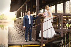 Bride and handsome groom walking down the stairs on pier Stock Photography