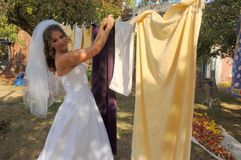 Bride hanging laundry Royalty Free Stock Photo