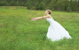 Bride hastens towards to groom on meadow Stock Photo