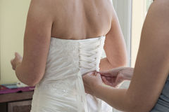 Bride having her dress laced up Stock Photo