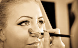 A bride having her make-up done. A bride in her wedding day, having a make-up done royalty free stock photos