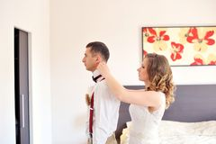 Bride helping to the groom dress shirt Royalty Free Stock Images