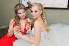 The bride and her bridesmaid with a glass of wine Royalty Free Stock Photo