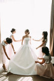 Bride and her bridesmaids next to the window Stock Photos