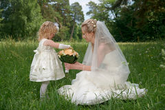 Bride with her daughter together with a bouquet on green summer. Field Royalty Free Stock Photo
