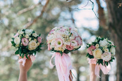 The bride and her friends held their wedding bouquets in hands Stock Image