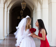 Bride and her Maid of Honor. Best friends in an outdoor beautiful hallway Royalty Free Stock Image
