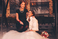 Bride and her sister laughing on bench Stock Photo