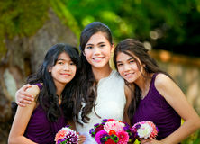 Bride with her two bridesmaid holding bouquet outdoors together. Biracial bride standing with her two bridesmaids outside, smiling and holding flower bouquet Royalty Free Stock Images