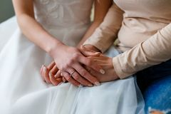 Bride on her wedding day holding her mother`s hands. Concept of. Relationship between moms and daughters, love and care Royalty Free Stock Photos