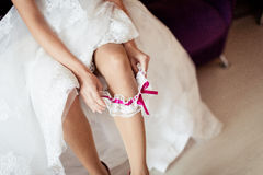 The bride on her wedding day. Morning bride. Close-up of young bride putting on white garter. Royalty Free Stock Photo