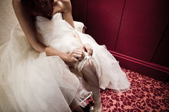 The bride on her wedding day. Morning bride. Close-up of young bride putting on white garter. Stock Images