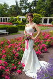 Bride in her white wedding dress and with bouquet of flowers Stock Photos