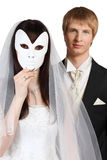 Bride hid face behind mask; groom stands behind. Beautiful bride hid her face behind white mask; groom stands behind her isolated on white background; focus on Stock Images