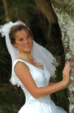 Bride hiding. A beautiful caucasian bride head portrait with happy expression in her pretty face wearing her white wedding dress and veil standing in the wind in Stock Images