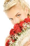 Bride hiding luxury bouquet. Beautiful bride hiding behind luxury bouquet of roses Stock Photography