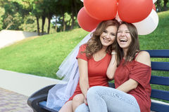 The bride with his girlfriend sitting in the park. Keep balloons Royalty Free Stock Photo